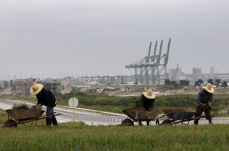 In this Nov. 6, 2013 photo, workers landscape the area near a new port under construction in Mariel, Cuba. Some companies will no doubt be hesitant to set up shop at the new port knowing that U.S. embargo rules would almost certainly prohibit them from selling their products in the United States, and that their Cuban operations could complicate any trade they do with Uncle Sam. Embargo rules prohibit ships from docking in the United States for six months after calling in Cuban ports. (AP Photo/Franklin Reyes)