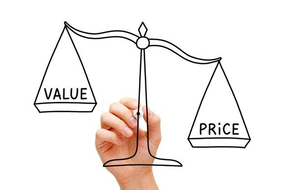 A hand drawing a scale weighing value and price