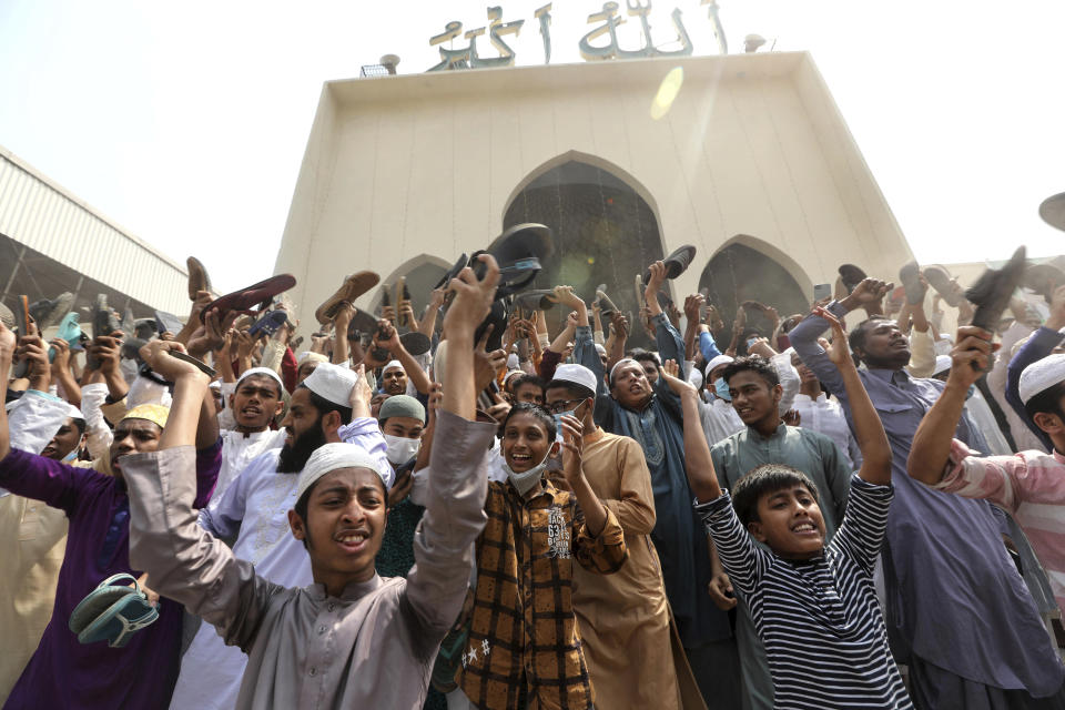 A group of protestors shout slogans and wave shoes after Friday prayers at Baitul Mokarram mosque in Dhaka, Bangladesh, Friday, March 26, 2021. Witnesses said violent clashes broke out after one faction of protesters began waving their shoes as a sign of disrespect to Indian Prime Minister Narendra Modi, and another group tried to stop them. Local media said the protesters who tried to stop the shoe-waving are aligned with the ruling Awami League party. The party criticized the other protest faction for attempting to create chaos in the country during Modi's visit. (AP Photo/Mahmud Hossain Opu)