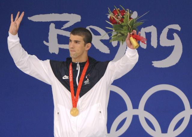 Gold medalist Michael Phelps of the United States waves during the awarding ceremony of the men's 200-meter butterfly final during the swimming competitions in the National Aquatics Center at the Beijing 2008 Olympics in Beijing, Wednesday, Aug. 13, 2008. Phelps set a world record in the event. (AP Photo/Mark J. Terrill)