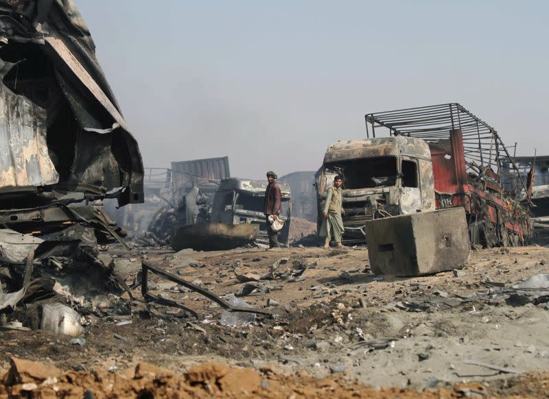 Men walk amidst wreckage of gas tankers after a fire in Islam Qala