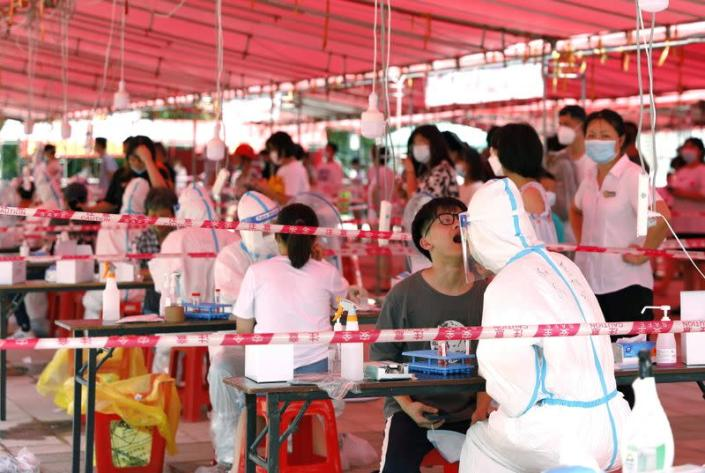 Medical workers conduct nucleic acid tests for residents following new cases of COVDI-19, in Xiamen