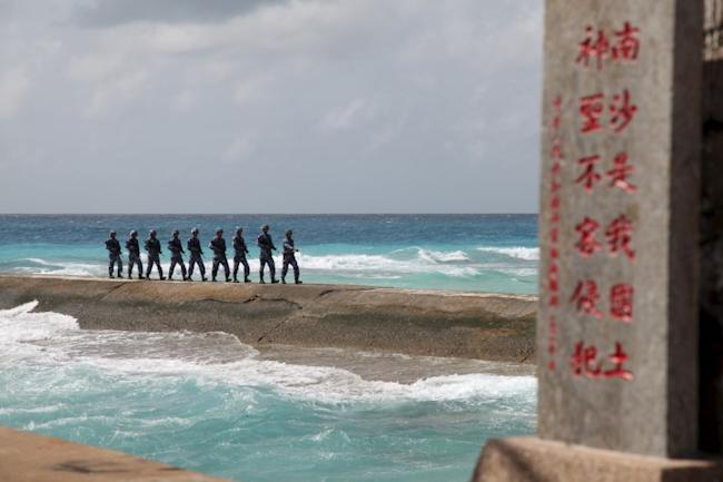 Soldiers of China's People's Liberation Army (PLA) Navy patrol near a sign in the Spratly Islands, known in China as the Nansha Islands, February 9, 2016. REUTERS/Stringer