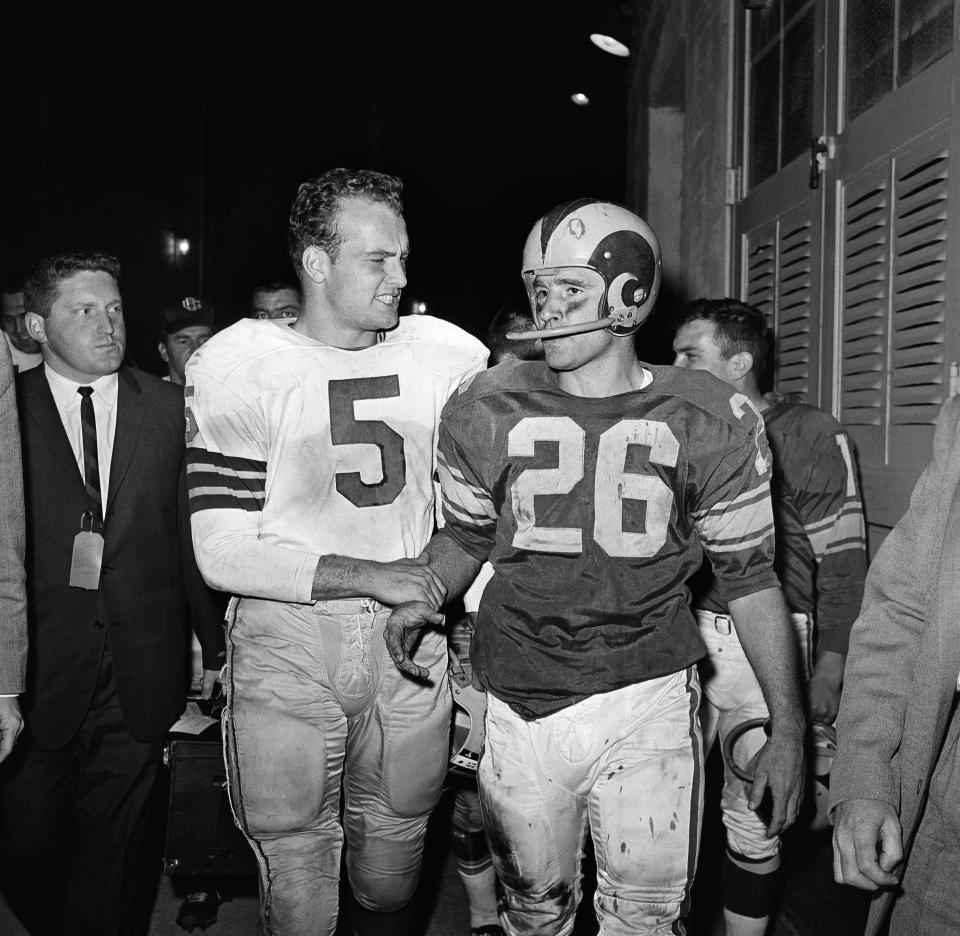 FILE - In this Dec. 17, 1960, file photo, halfback Paul Hornung, left, one of the stars of Green Bay's 35-21 victory over the Los Angeles Rams in the Los Angeles Memorial Coliseum, offers a word of consolation to Ram's halfback Jon Arnett after the game in Los Angeles. Hall of Fame halfback Jon Arnett, one of University of Southern California's greatest running backs who then starred with the Los Angeles Rams, died on Saturday, Jan. 16, 2021, of heart failure in Lake Oswego, Ore. He was 85. (AP Photo/Harold Matosian, File)