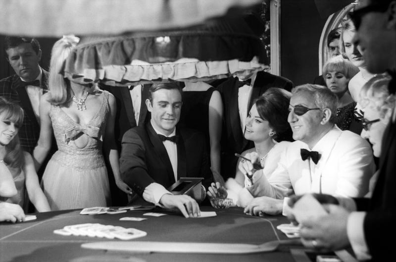 The actors Sean Connery, Claudine Auger and Adolfo Celi prepare the scene at the casino from the movie Thunderball by Terence Young, fourth episode of secret agent 007's series. Pinewood (London), march 1965. (Photo by Mario De Biasi/Mondadori via Getty Images)