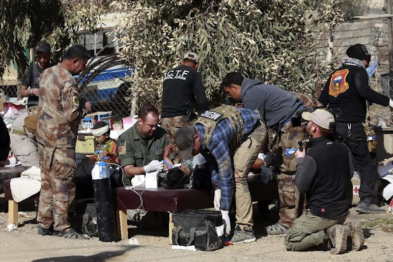 Army paramedics give first aid to displaced civilians, injured in IS mortar bombing, during fighting between Iraqi security forces and Islamic State militants, in the western side of Mosul, Iraq, Sunday, Feb. 26. 2017. (AP Photo/ Khalid Mohammed)