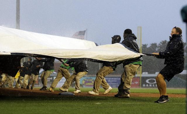Members of the Roger Dean Stadium grounds crew struggle with a tarp as rain halts an exhibition spring training baseball game between the Miami Marlins and the Boston Red Sox during the eighth inning Thursday, March 6, 2014, in Jupiter, Fla. (AP Photo/Jeff Roberson)