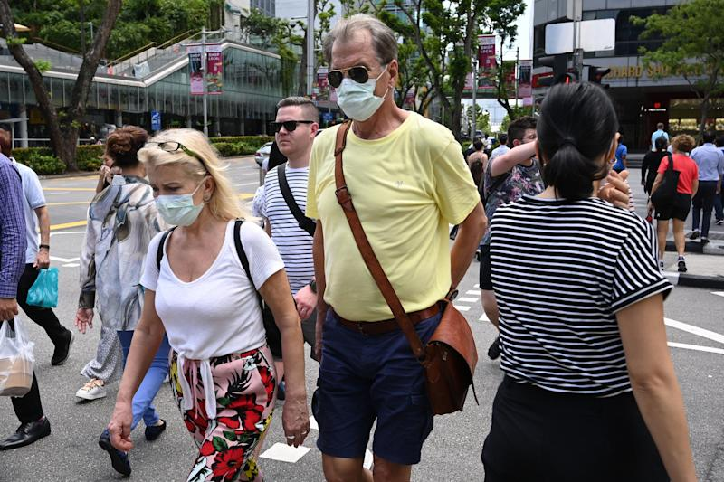 A couple wearing protective facemasks amid fears about the spread of the COVID-19 coronavirus cross a road in Singapore on February 26, 2020. (Photo by ROSLAN RAHMAN / AFP) (Photo by ROSLAN RAHMAN/AFP via Getty Images)