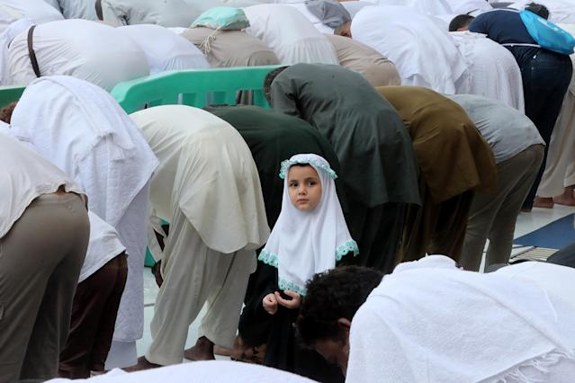 <p>A young girl looks on as Muslim pilgrims pray at the Grand Mosque in the holy Saudi city of Mecca, on Aug. 29, 2017, on the eve of the start of the annual hajj pilgrimage. (Photo: Karim Sahib/AFP/Getty Images) </p>