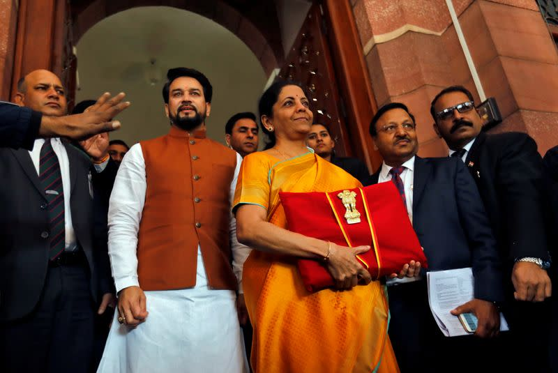 India's Finance Minister Nirmala Sitharaman is flanked by junior Finance Minister Anurag Thakur as she arrives to present the budget in Parliament in New Delhi