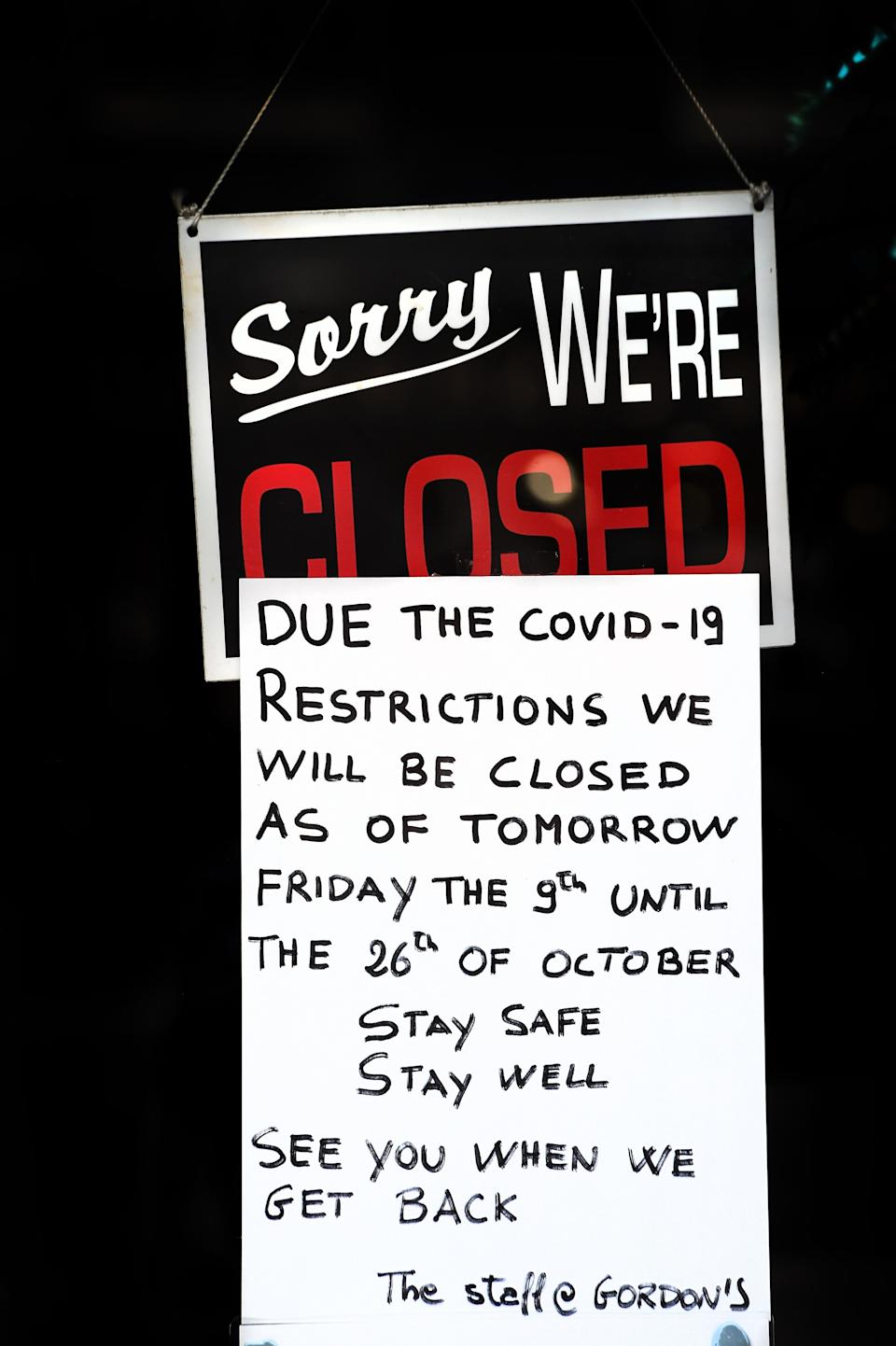 A sign explaining their temporary closure is seen on the door of a restaurant in Edinburgh on October 9, 2020, as new restrictions come into force to combat the spread of coronavirus covid-19. - Scotland has ordered a two-week closure of pubs in the central part of the country including the main cities Glasgow and Edinburgh, as ministers try to curb a rise in coronavirus cases. (Photo by ANDY BUCHANAN / AFP) (Photo by ANDY BUCHANAN/AFP via Getty Images)