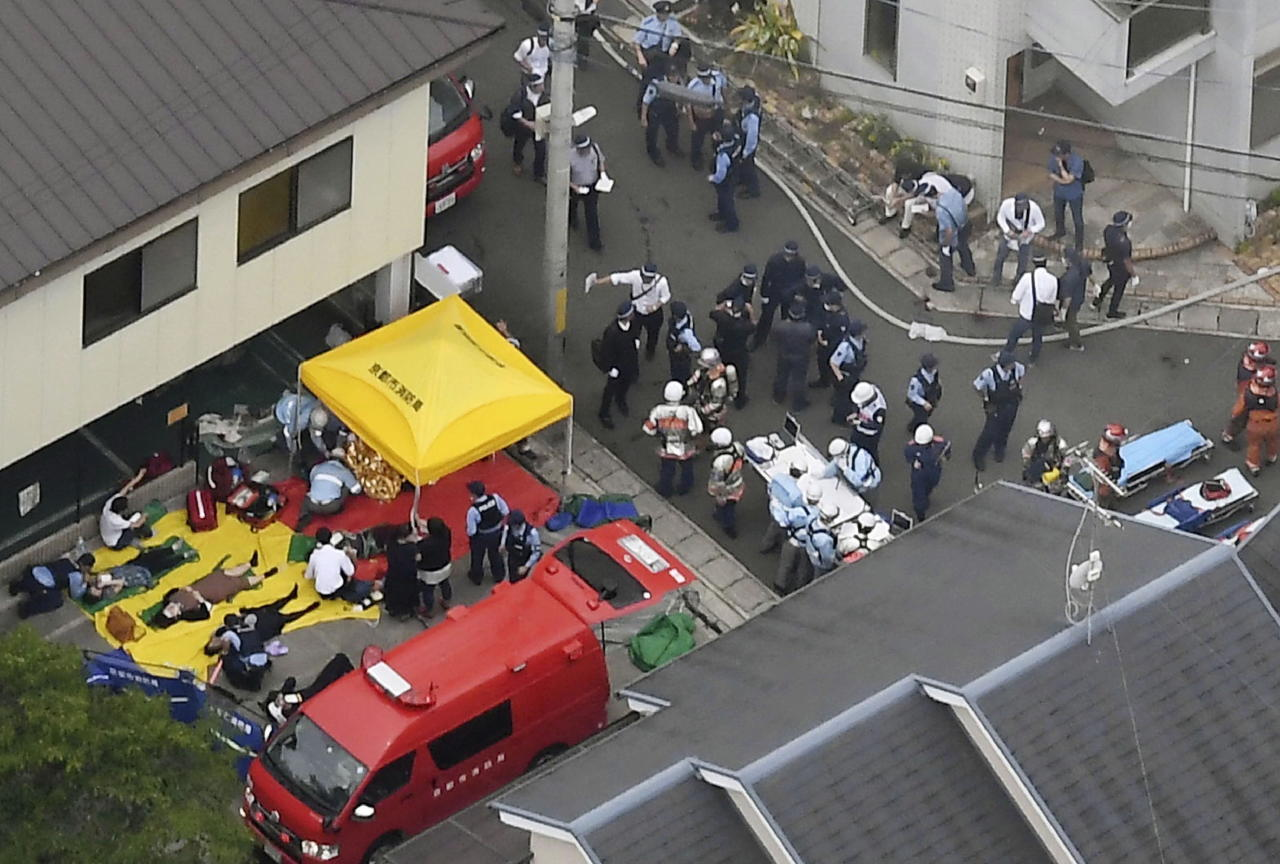 People injured are treated near the Kyoto Animation building in Kyoto, western Japan.(Kyodo News via AP)