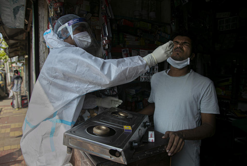A health worker takes a nasal swab sample of a shopkeeper during random testing for COVID-19 in a market in Gauhati, India, Friday, Oct. 16, 2020. India's coronavirus fatalities jumped by 895 in the past 24 hours, a day after recording the lowest daily deaths of 680 in nearly three months. The Health Ministry on Friday also reported 63,371 new cases in the past 24 hours, raising India's total to more than 7.3 million, second in the world behind the U.S. (AP Photo/Anupam Nath)