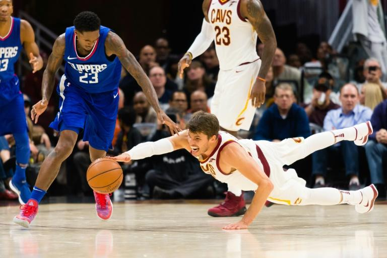 Lou Williams (L) of the LA Clippers and Kyle Korver of the Cleveland Cavaliers dive for a loose ball at Quicken Loans Arena