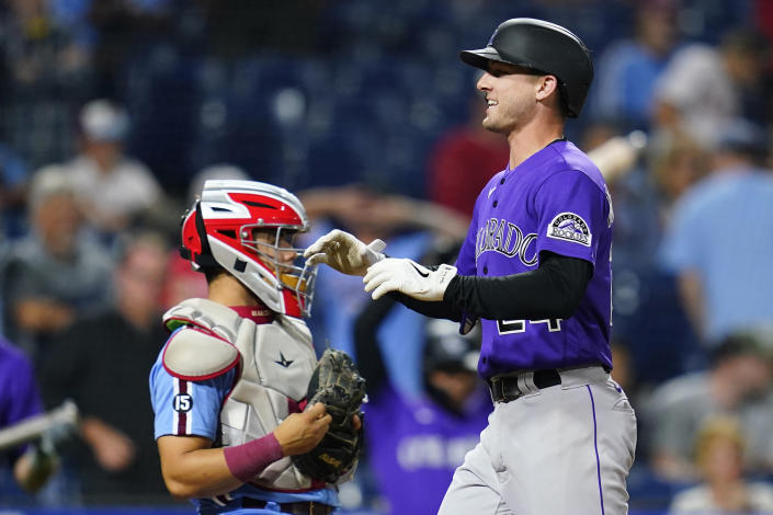 Colorado Rockies' Ryan McMahon, right, celebrates past Philadelphia Phillies catcher Rafael Marchan after hitting a two-run home run against pitcher Ian Kennedy during the ninth inning of a baseball game, Thursday, Sept. 9, 2021, in Philadelphia. (AP Photo/Matt Slocum)