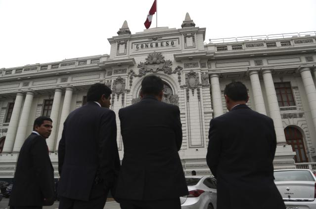 Security officers stand outside Congress where lawmakers are expected to push forward a vote to select an almost-full slate of new magistrates to the Constitutional Tribunal, in Lima, Peru, Monday, Sept. 30, 2019. Lawmakers are pushing forward the vote despite President Martín Vizcarra's warning the move threatens his fight against corruption and that he'll dissolve the opposition-controlled legislature. (AP Photo/Martin Mejia)