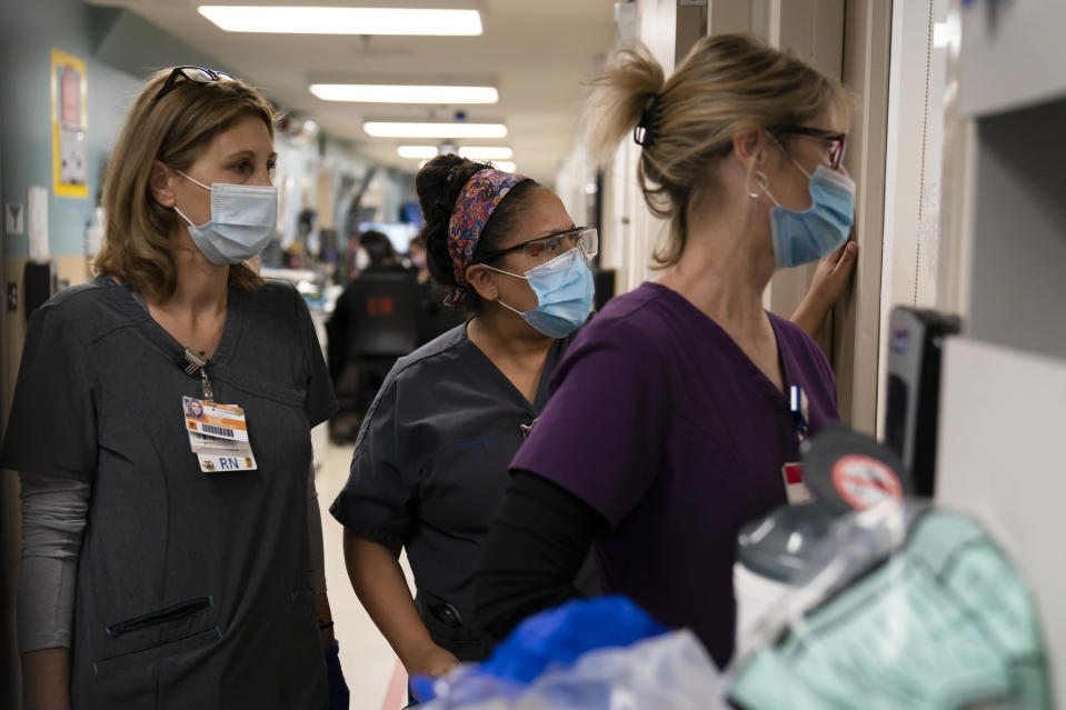FILE - In this Nov. 19, 2020, file photo, registered Nurse Kristina Shannon, from left, chaplain Andrea Cammarota, and Emergency Room charge nurse Cathy Carter watch as medical workers try to resuscitate a patient who tested positive for coronavirus in the emergency room at Providence Holy Cross Medical Center in the Mission Hills section of Los Angeles. The surge of coronavirus is taking an increasingly grim toll across the United States, even as of a vaccine appears close at hand. (AP Photo/Jae C. Hong, File)