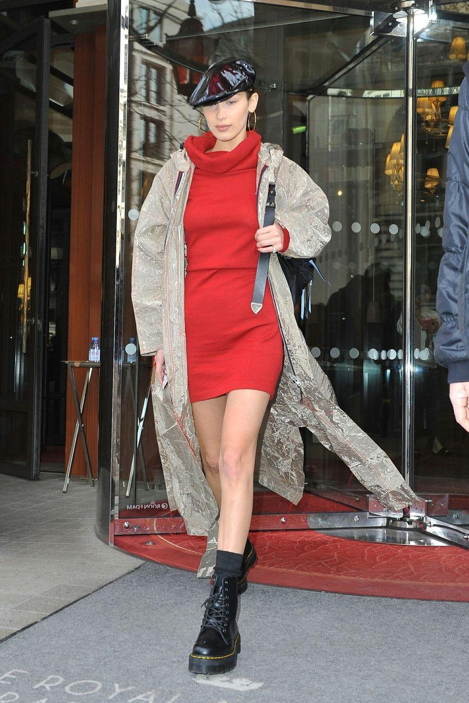 <p>In a bright red turtleneck mini dress, under a long taupe rain jacket, with lace-up combat boots, large gold hoop earrings, and a black vinyl PVC newsboy cap walking out of her hotel in Paris.</p>