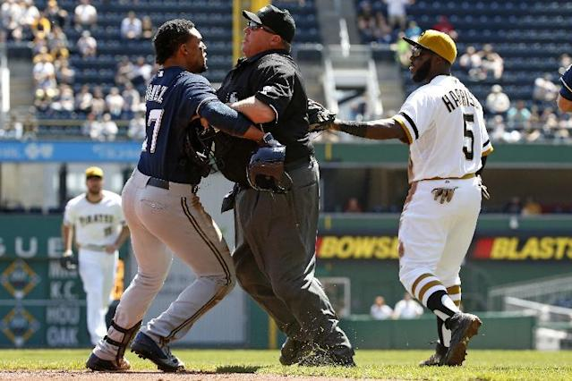 Milwaukee Brewers' Carlos Gomez, left, tries to get past umpire Fieldin Culbreth, center, as Pittsburgh Pirates third baseman Josh Harrison (5) tries to get to Pirates starting pitcher Gerrit Cole during the third inning of a baseball game in Pittsburgh, Sunday, April 20, 2014. A dugouts clearing brawl ensued. (AP Photo/Gene J. Puskar)