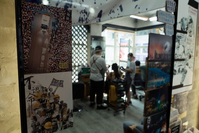 Pro-democracy signs and postcards are seen on a mirror at Hair Guy Salon, in Hong Kong