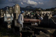 Cemetery workers carry the coffin that contains the remains of 89-year-old Irodina Pinto Ribeiro, who died from COVID-19 related complications, at the Inhauma cemetery in Rio de Janeiro, Brazil, Friday, June 18, 2021. Brazil is approaching an official COVID-19 death toll of 500,000 — second-highest in the world. (AP Photo/Bruna Prado)
