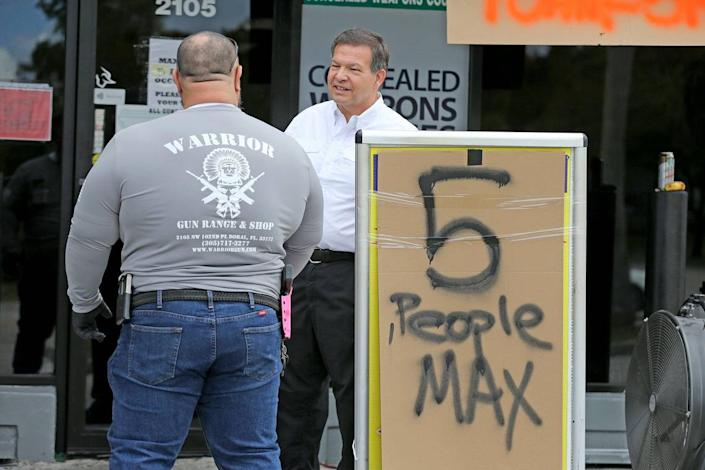 Gun shop owner Charlie Berrane talks to his employee outside Warriors Gun Range and Gun Shop in Doral, March 24, 2020. The shop is experiencing soaring sales of guns and ammo as people worry about the repercussions of the coronavirus pandemic.