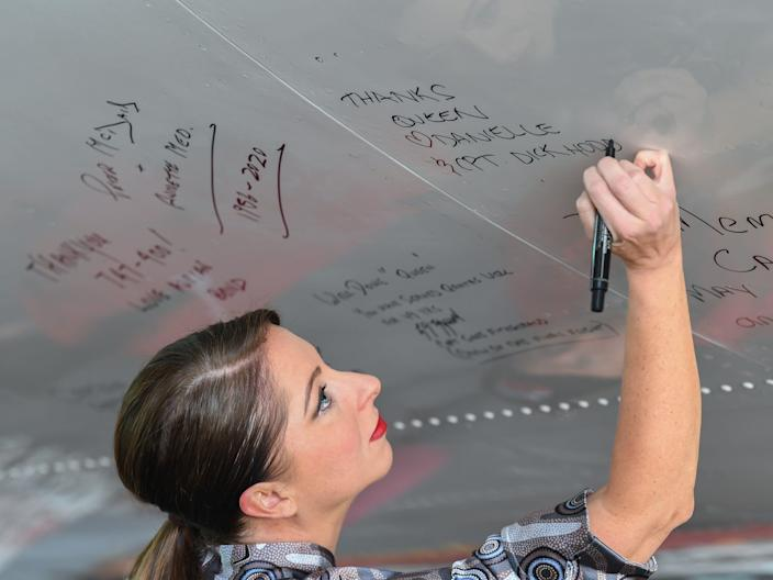 A Qantas employee signing the fuselage of the last 747 flying for the airline.