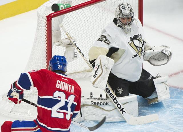 Pittsburgh Penguins goaltender Marc-Andre Fleury, right, keeps an eye on the play as Montreal Canadiens right winger Brian Gionta moves in on the net during first-period NHL hockey game action in Montreal, Saturday, Nov. 23, 2013. (AP Photo/The Canadian Press, Graham Hughes)