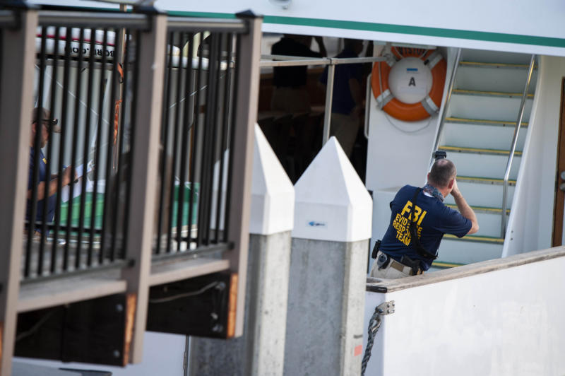"""FBI investigators climb aboard the """"Vision"""" a sister vessel to the scuba boat Conception to document its layout and learn more about the deadly pre-dawn fire in Santa Barbara, Calif., on Tuesday, Sept. 3, 2019. A fire raged through the boat carrying recreational scuba divers anchored near an island off the Southern California Coast on Monday, leaving multiple people dead. Authorities on Tuesday ended the search for survivors. (AP Photo/Christian Monterrosa)"""