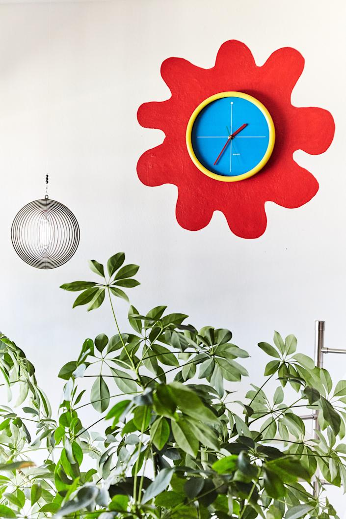 """Leah created her version of an indoor garden using a laser-cut metal hanging—a gift from her sister, who lives in South Africa—hung above a tree next to an unconventional sun. """"Love that clock. It's from the '80s, obviously, and then I painted that red squiggle around it. It's my favorite moment in my apartment probably."""""""