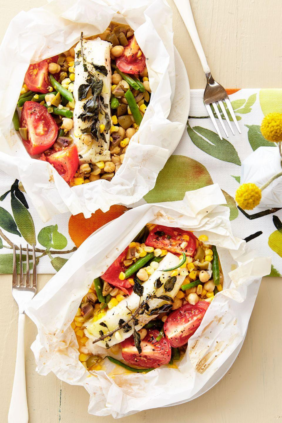 """<p>Get dinner on the table quick (and keep dirty dishes to a minimum) with these simple fish packets.</p><p><strong><a href=""""https://www.countryliving.com/food-drinks/recipes/a38076/bass-packets-with-tomato-corn-chickpeas-and-olives-recipe/"""" rel=""""nofollow noopener"""" target=""""_blank"""" data-ylk=""""slk:Get the recipe"""" class=""""link rapid-noclick-resp"""">Get the recipe</a>.</strong></p>"""