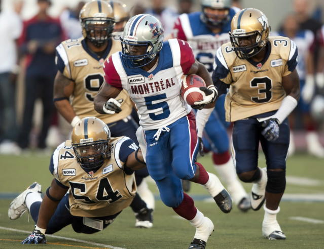 Montreal Alouettes running back Noel Devine tries to evade Winnipeg Blue Bombers Kenny Mainor(54) and Dustin Doe(3) during first quarter Canadian Football League pre-season action Thursday, June 14, 2012 in Montreal. THE CANADIAN PRESS/Ryan Remiorz