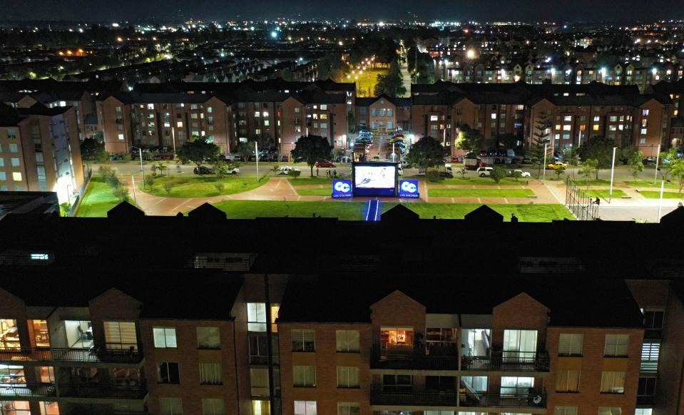 Aerial view as a film is projected on a giant screen at a park, so that quarantined people in their apartments watch a movie from home amid the coronavirus (COVID-19) pandemic, in Bogota, on April 23, 2020. - Colombia extended mandatory preventive isolation due to COVID-19 until at least May 11. (Photo by Raul ARBOLEDA / AFP) (Photo by RAUL ARBOLEDA/AFP via Getty Images)