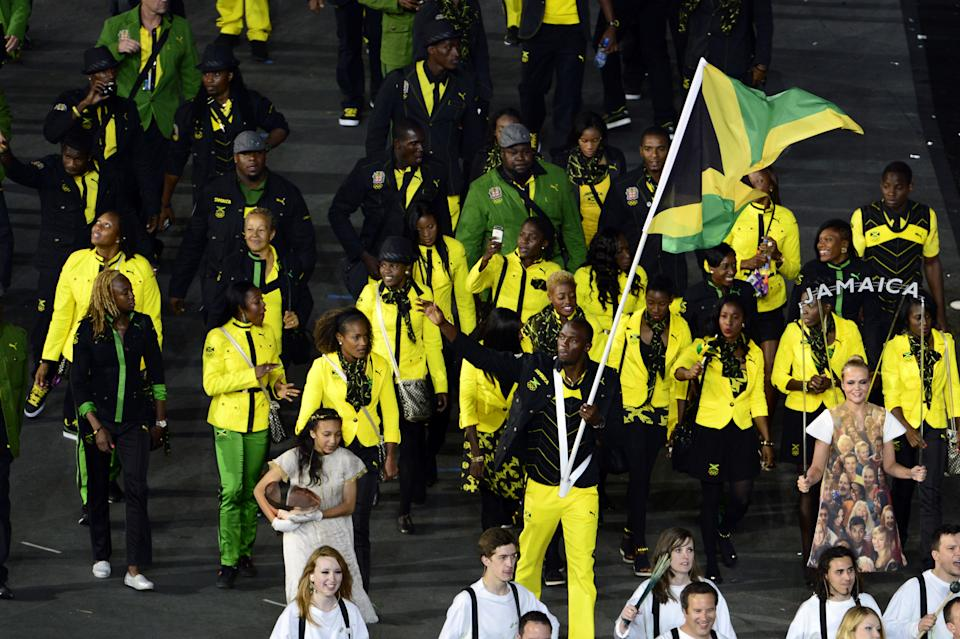 Jamaica's flagbearer Usain Bolt leads his delegation during the opening ceremony of the London 2012 Olympic Games in the Olympic Stadium in London on July 27, 2012.  AFP PHOTO / JOHN MACDOUGALL        (Photo credit should read JOHN MACDOUGALL/AFP/GettyImages)