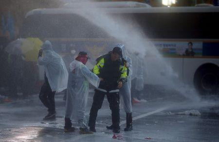 A riot policeman is held by protesters as water mixed with tear gas liquid is sprayed by police water canon to disperse protesters during an anti-government rally in central Seoul