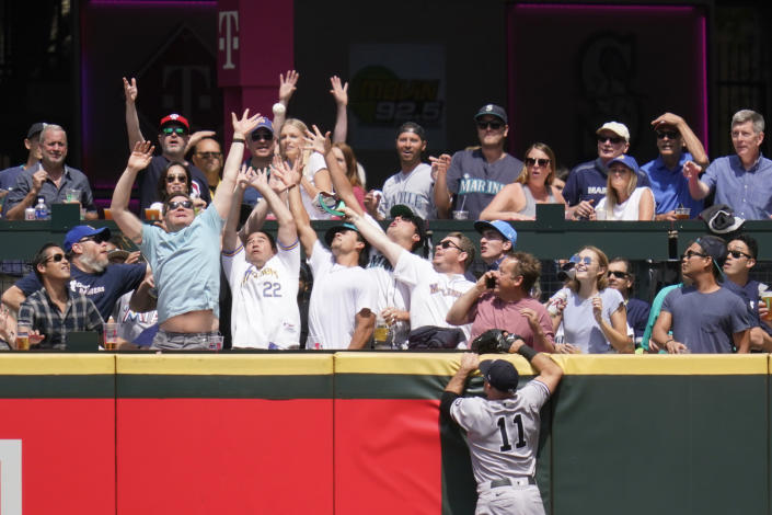 New York Yankees center fielder Brett Gardner (11) watches as fans reach for the home run ball of Seattle Mariners' Dylan Moore in the second inning of a baseball game Thursday, July 8, 2021, in Seattle. (AP Photo/Elaine Thompson)
