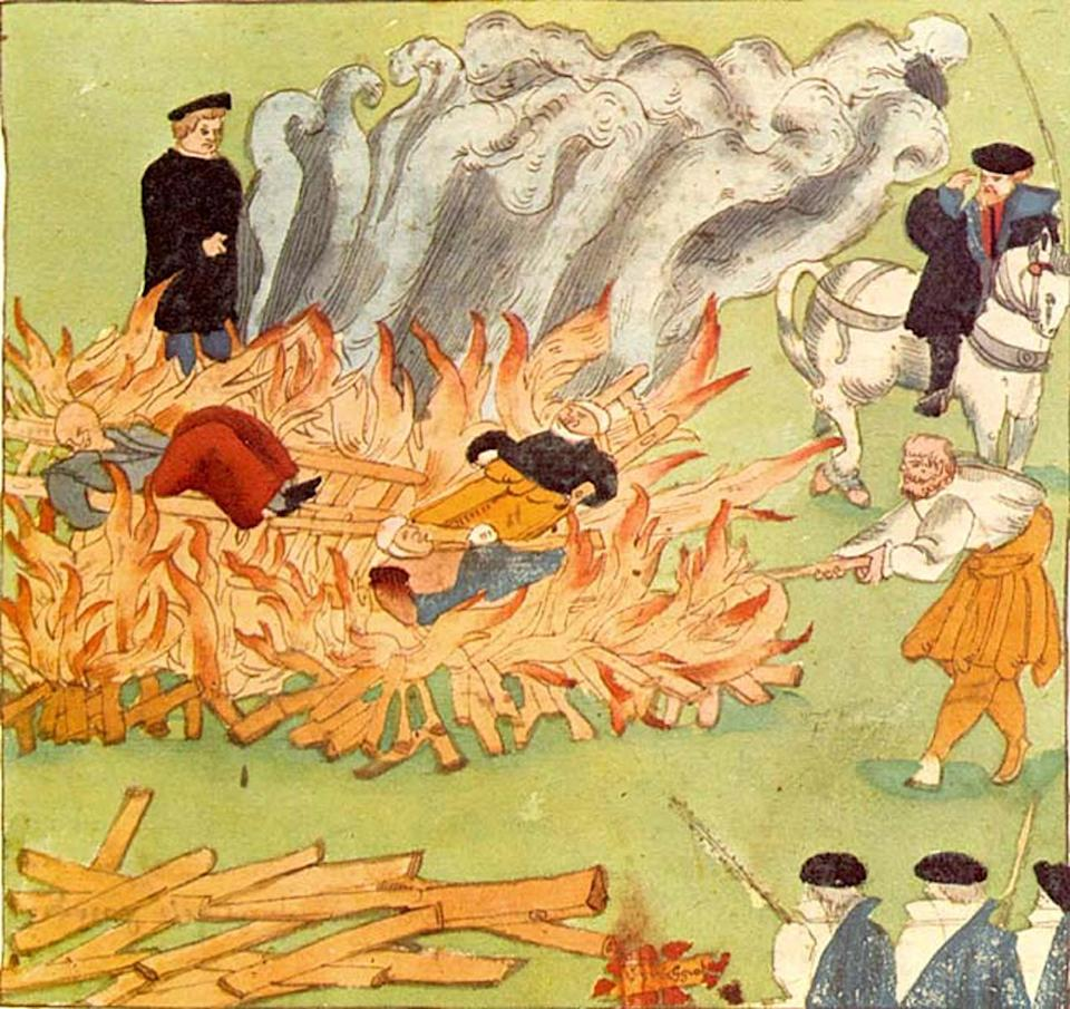 An illustration depicting witches in the fire as a clergyman watches.