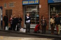 People wait at a bus stop in front of an Asian shop after shopping in downtown Malaga, southern Spain May 4, 2012. The euro zone economy worsened markedly in April, according to business surveys. (REUTERS/Jon Nazca)