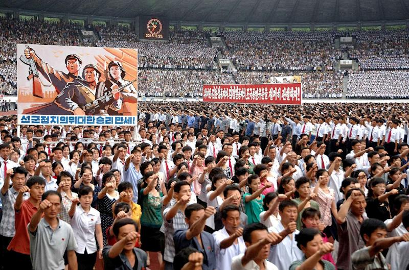 North Korean people raise their fists during an anti-US rally at Kim Il-Sung stadium in Pyongyang on June 25, 2015