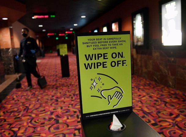 PHOTO: In this Aug. 14, 2020, file photo, an employee cleans a hallway as he walks by a seat wipe station at a theater in Las Vegas. (Ethan Miller/Getty Images, FILE)