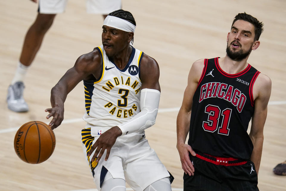 Indiana Pacers guard Aaron Holiday (3) passes the ball away from Chicago Bulls guard Tomas Satoransky (31) during the first half of an NBA basketball game in Indianapolis, Tuesday, April 6, 2021. (AP Photo/Michael Conroy)