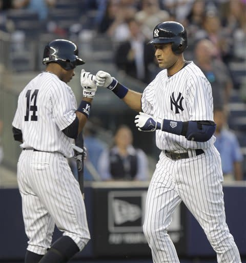 New York Yankees' Derek Jeter, right, is greeted by Curtis Granderson after Jeter hit a home run during the first inning of a baseball game against the Minnesota Twins at Yankee Stadium in New York, Monday, April 16, 2012. (AP Photo/Seth Wenig)