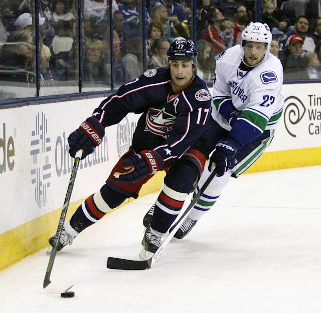 Columbus' Brandon Dubinsky (17) skates away from Vancouver's Alexander Edler during the second period of an NHL hockey game Sunday, Oct. 20, 2013, in Columbus, Ohio. (AP Photo/Mike Munden)