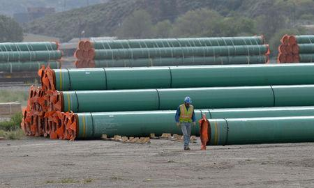 FILE PHOTO: A workman walks past steel pipe to be used in the pipeline construction of the Trans Mountain Expansion Project at a stockpile site in Kamloops