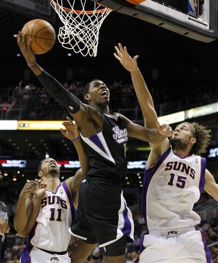 Sacramento Kings center Jason Thompson, left, shoots over Phoenix Suns center Robin Lopez in the second quarter during an NBA basketball game on Sunday, March 4, 2012, in Phoenix, Ariz. (AP Photos/Rick Scuteri)