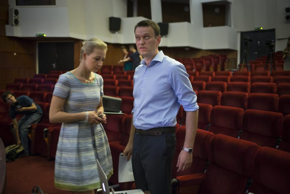 FILE - In this Monday, July 1, 2013 file photo, Alexei Navalny, Russian opposition leader, right, and his wife, Yulia, arrive to present his campaign platform in Moscow. Navalny's energy and charisma propelled him from a lonely role blogging about corruption to widely renown as Russia's leading opposition activist. His projects, including a campaign to run for Moscow mayor, have attracted hordes of volunteers and fundraisers. Now comes a day that looms large for Navalny and the opposition: A court hands down its verdict Thursday in an embezzlement case that could send him to prison for six years. (AP Photo/Alexander Zemlianichenko, File)