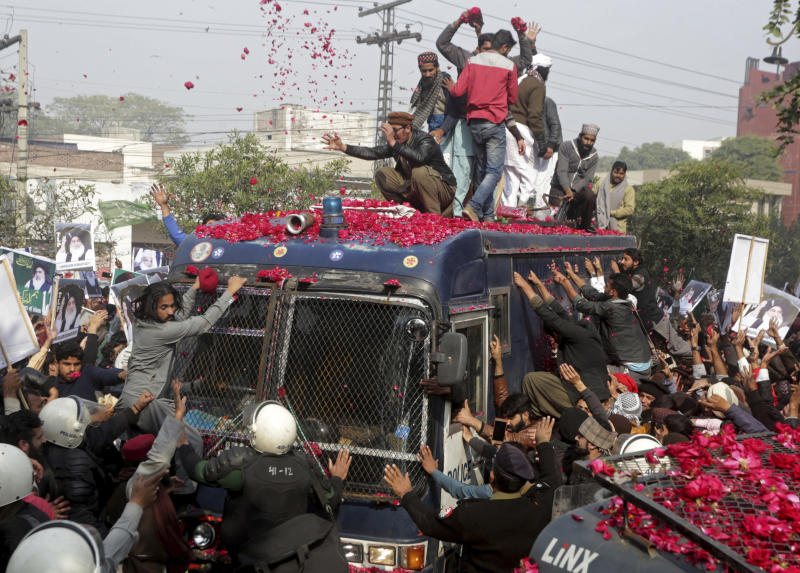 FILE - In this Feb. 4, 2019 file photo, supporters of Tehreek-e-Labbaik, a Pakistani religious group, surround an armored police armored car carrying their leader, Khadim Hussain Rizvi, as he arrives to a court in Lahore, Pakistan. A Pakistani court has sentenced 86 members of the radical Islamist party to 55-year prison terms each for taking part in violent rallies in 2018 over the acquittal of a Christian woman in a blasphemy case, a party official said Friday.(AP Photo/K.M. Chaudary, File)