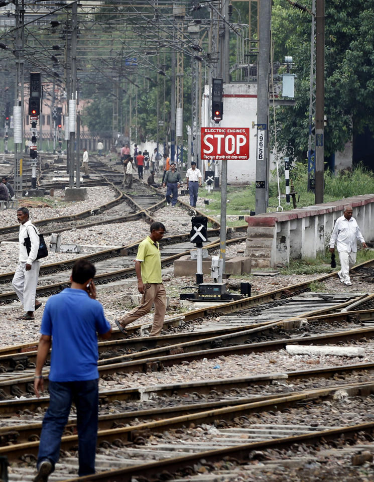 Commuters walk on empty railway tracks at the New Delhi railway station following a power outage in New Delhi, India, Tuesday, July 31, 2012. India's energy crisis cascaded over half the country Tuesday when three of its regional grids collapsed, leaving more than 600 million people without government-supplied electricity in one of the world's biggest-ever blackouts. (AP Photo/Mustafa Quraishi)