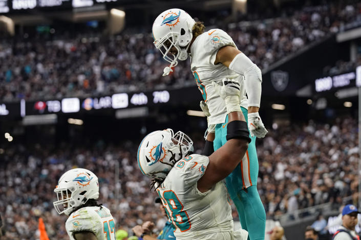 Miami Dolphins offensive guard Robert Hunt (68) holds up wide receiver Will Fuller (3) after Fuller scored a two-point conversion against the Las Vegas Raiders during the second half of an NFL football game, Sunday, Sept. 26, 2021, in Las Vegas. (AP Photo/Rick Scuteri)