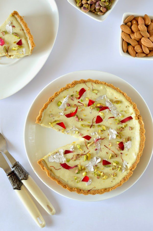 """<p><b>Ingredients</b></p><p>Cheesecake Base</p><p>1.5 cups Digestive Biscuit crumbs. </p><p>2 tbsps Sugar.<br>5 tbsps Butter melted,cooled.</p><p> For Cheesecake filling</p><p>1 cup Fresh cottage cheese(paneer) (water drained completely).<br> ½ cup thick Yoghurt. <br>1 cup Whipping cream. <br>¾ cup Sugar .<br>Pinch of 1 tsp Saffron soaked in warm milk.</p><p>1 tbsps Gelatin (bloomed in 1 tbsp boiling water). </p><p>1 tbsp Rose water 2 drops Or rose essence. </p><p>For Thandai </p><p>Mix: 40 Almonds ,10 Cashews, 2 tbsps Melon seeds, 1 tbsp Poppy seed, 2 tsps Fennel (saunf), 4 Cardamom, 1 tsp White/black peppercorn Pistachio,rose petal for garnishing.</p><p><b>Method</b></p><p>Soak almond in water at least 3-4 hours in a bowl. In a separate bowl soak cashew,melon seed and poppy seeds for 3-4 hours. Peel the almonds. Grind together almonds, cashew, melon, poppy seeds, fennel seeds, cardamom and peppercorn with little water and make a fine paste. This paste can be made a day or two ahead and kept refrigerated. </p><p>In a bowl mix together the biscuit crumbs, sugar, and melted butter. Press onto the bottom and up the sides of a well greased 8-9 inch tart pan with removable bottom. (A spring form pan can also be used). Place in the refrigerator to set while you make the filling. If you want you can bake the base for 10 minutes at 180 degree, it is optional.</p><p> In a blender blend cheese, yoghurt, cream, saffron infused milk, sugar, gelatin mixture and rosewater until everything is well incorporated. Add 1/3 cup of above thandai mixture and give one more whisk. Pour the mixture into the biscuit base, smooth the top. Cover and refrigerate at least 5 hours or overnight.</p><p>Images and Recipe Courtesy : <a href=""""http://www.theflavoursofkitchen.com/no-bake-thandai-cheesecake-recipe"""" rel=""""nofollow noopener"""" target=""""_blank"""" data-ylk=""""slk:The Flavours of Kitchen"""" class=""""link rapid-noclick-resp"""">The Flavours of Kitchen </a>by Subhasmita Panigrahi.</p>"""